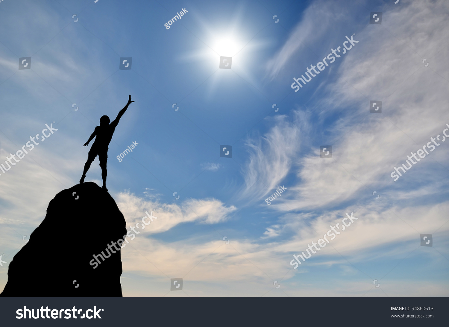 pic stock photo man on top of the mountain looking to the sun.