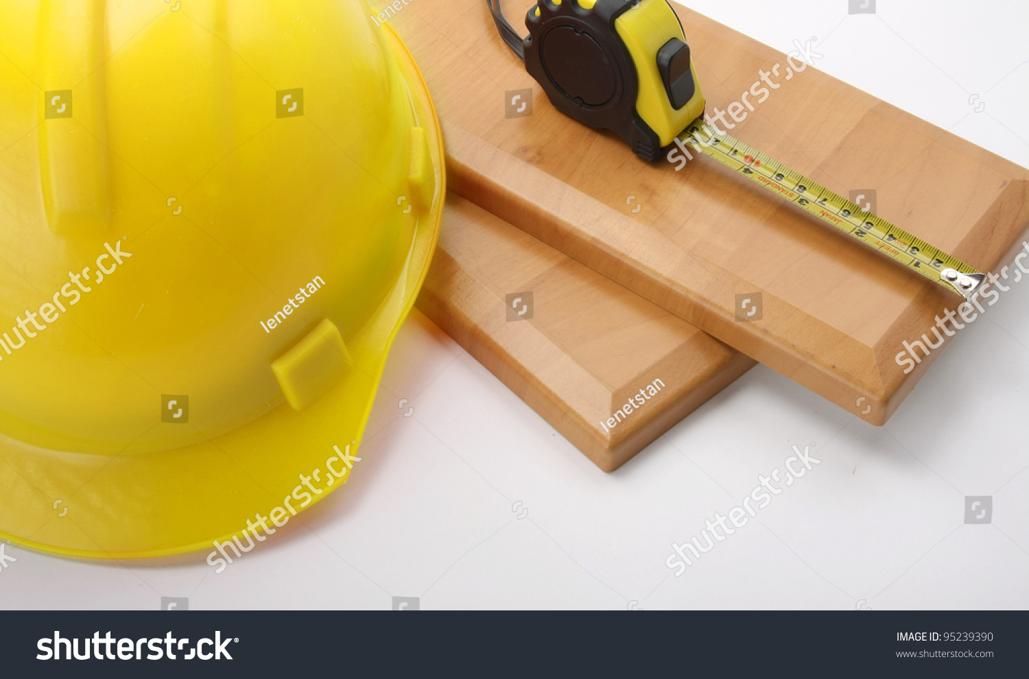 an orange hardhat with a ruler on wooden planks stock