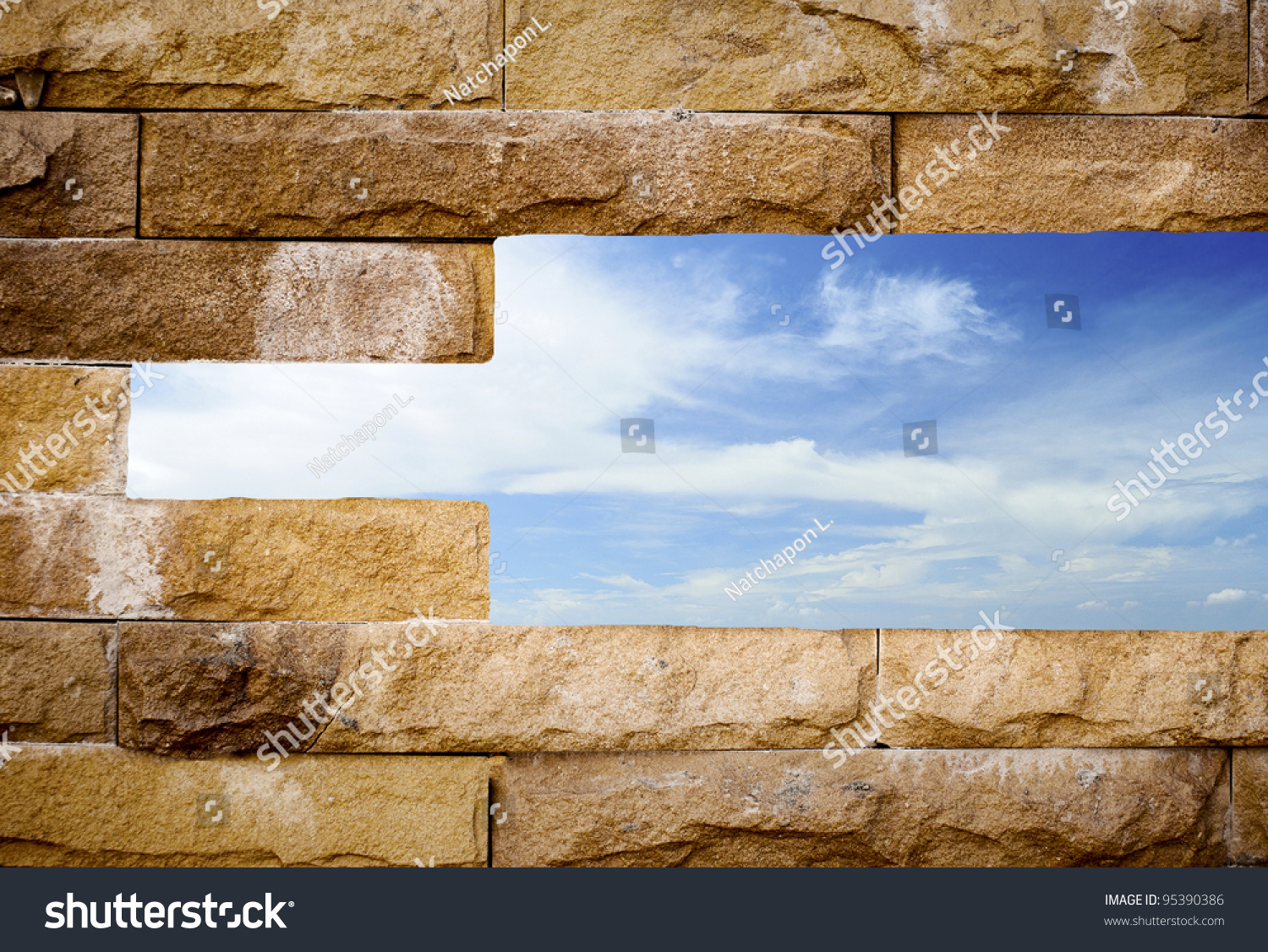 Brick Wall With A Hole With Blue Sky Background Stock