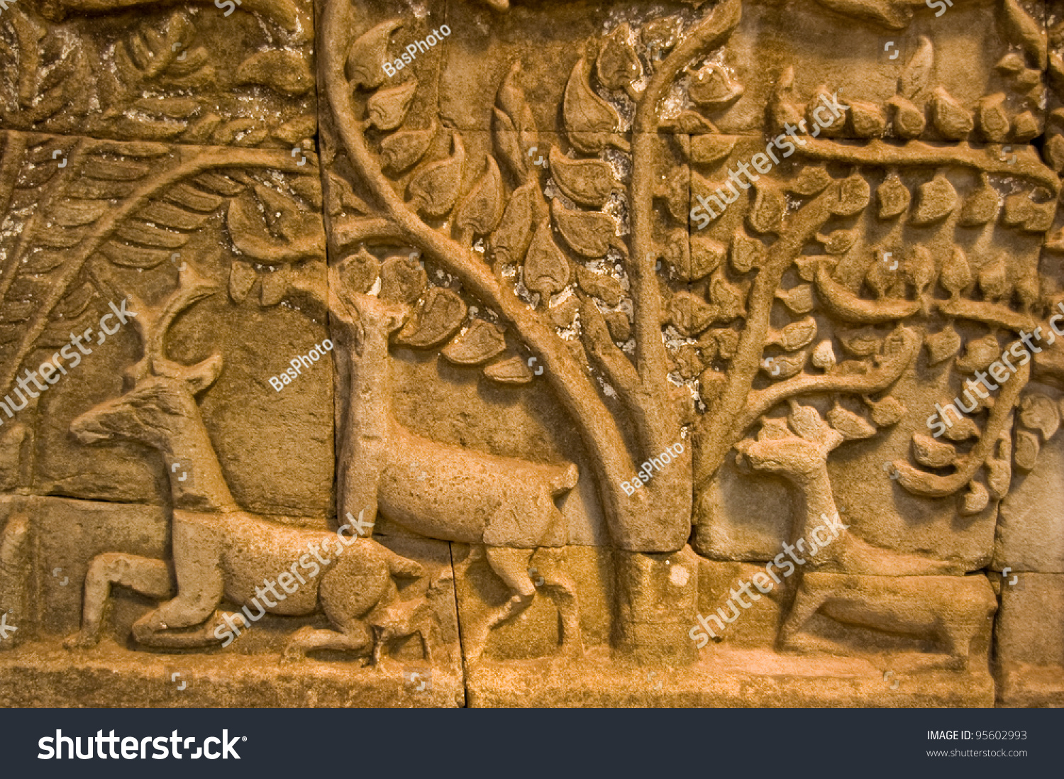 Ancient bas relief carving showing deer in a forest wall
