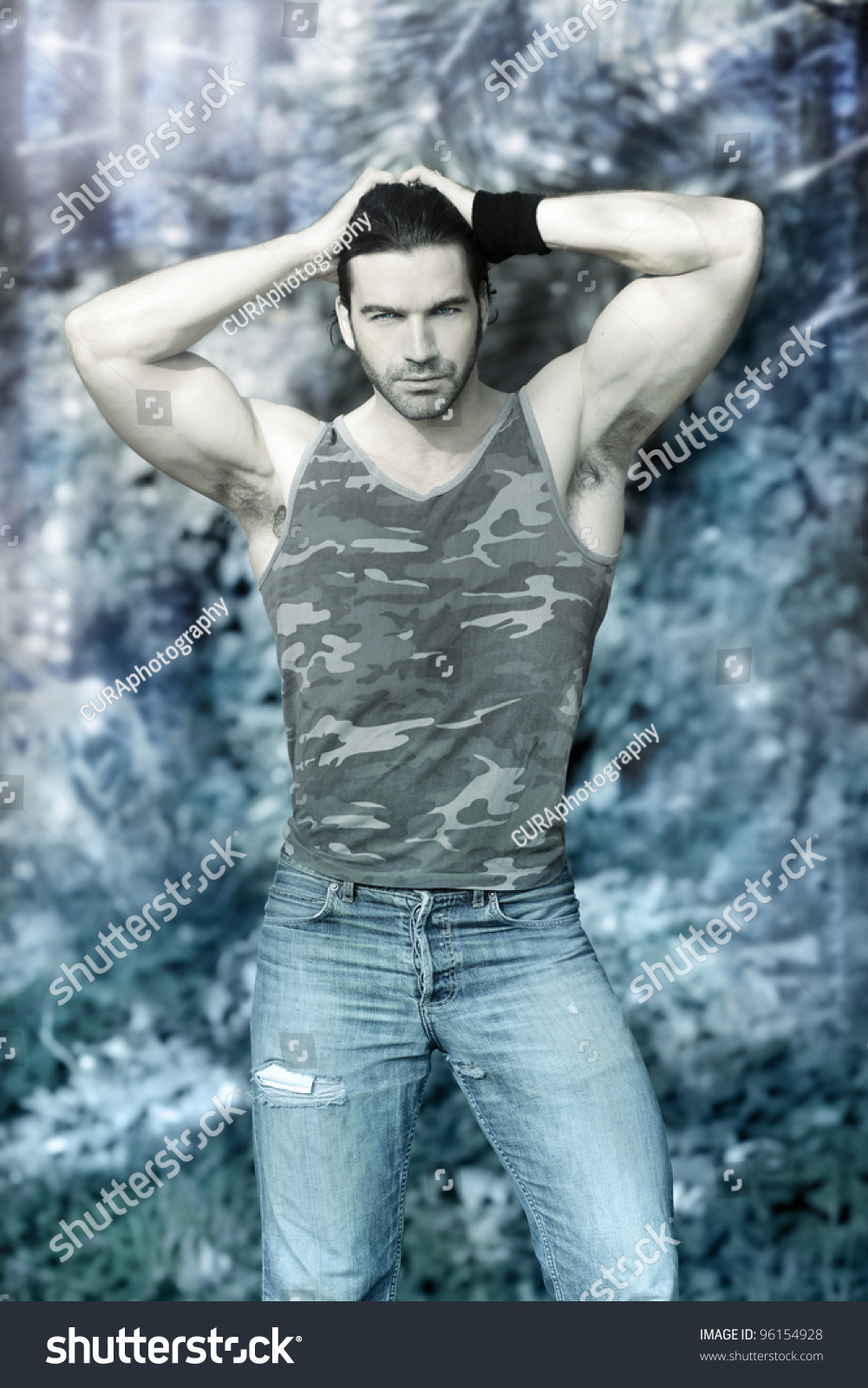 Stylized Outdoor Portrait Of Muscular Man Posing In Tank Top And Jeans Against Winter Wonderland Background