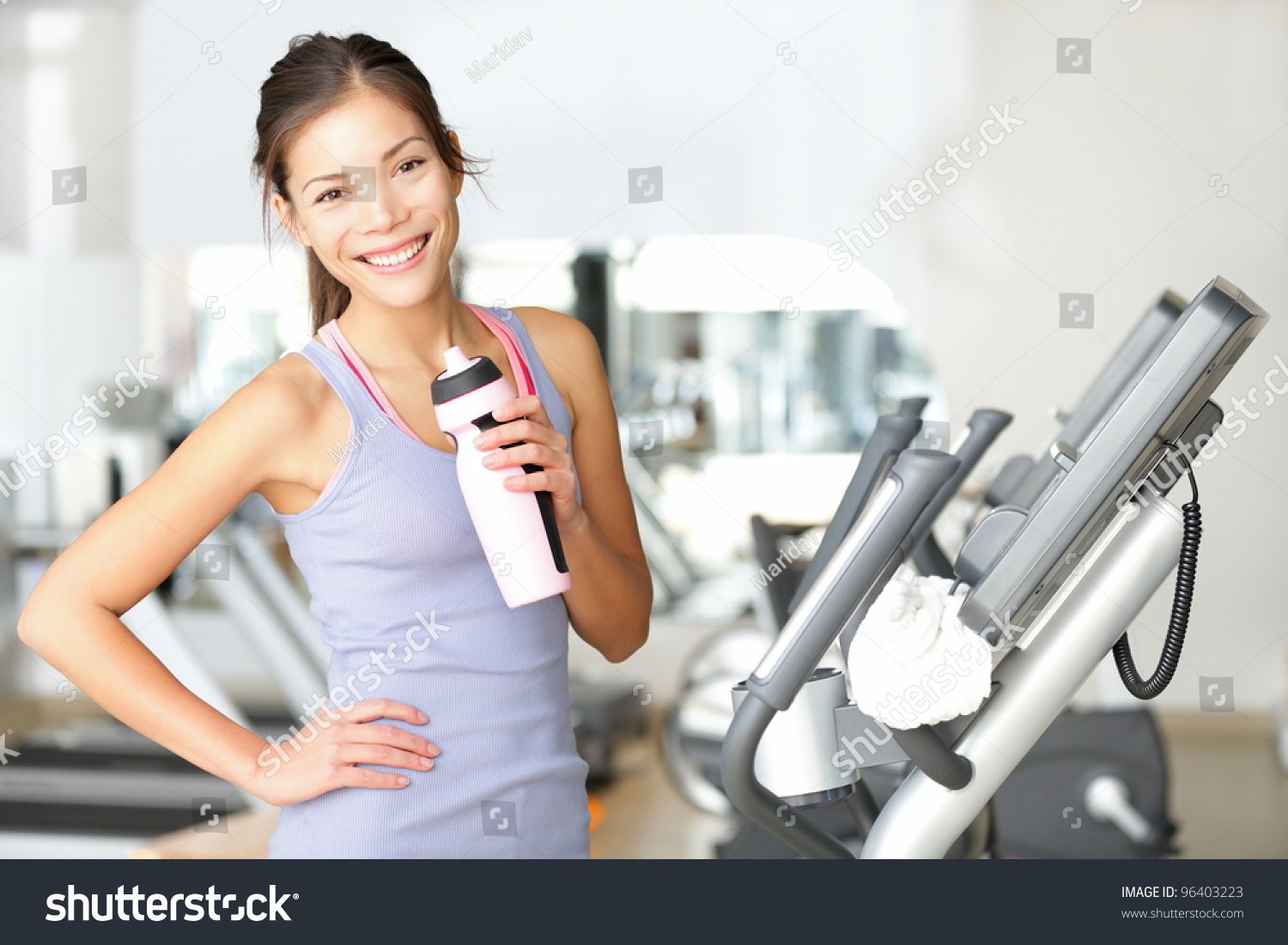 Royalty free gym woman working out drinking water 96403223 stock gym woman working out drinking water smiling happy standing by moonwalker fitness machines beautiful fit sciox Choice Image