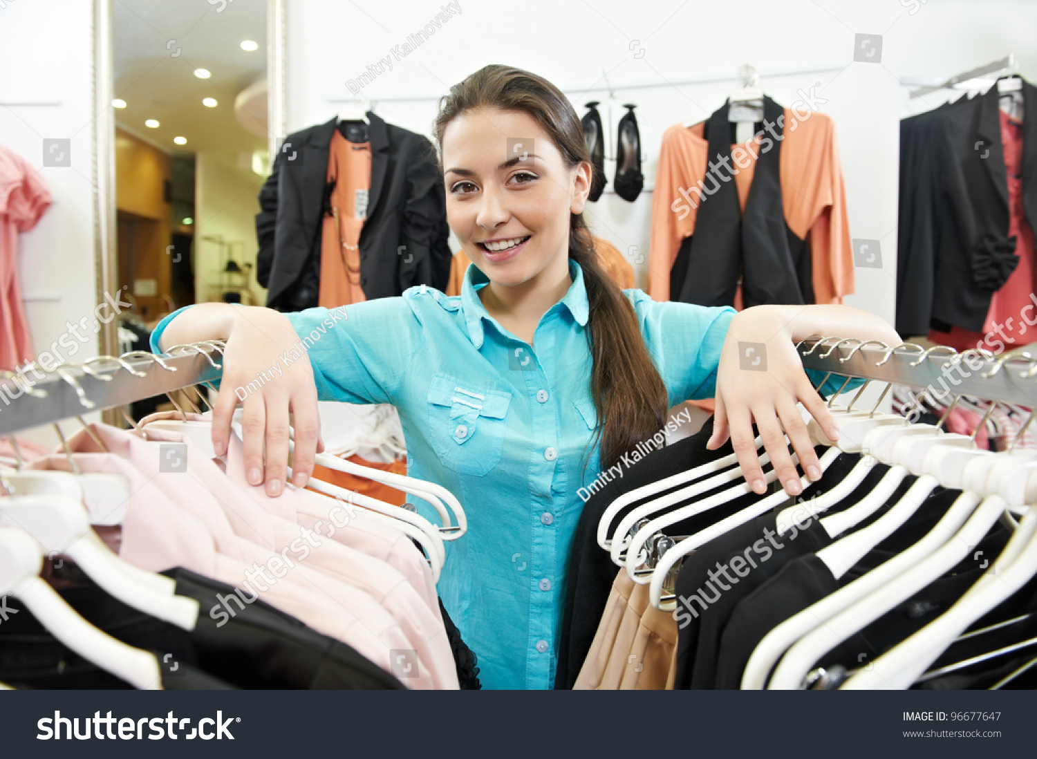 young smiling w seller assistant hands stock photo  young smiling w seller assistant hands on clothing hangers at shopping store