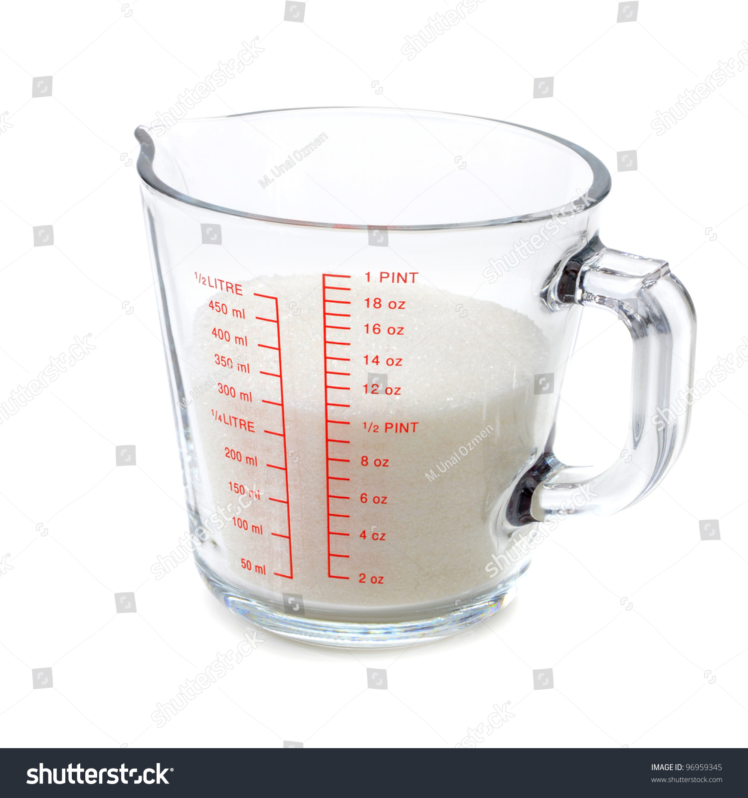 sugar in measuring cup on white background stock photo