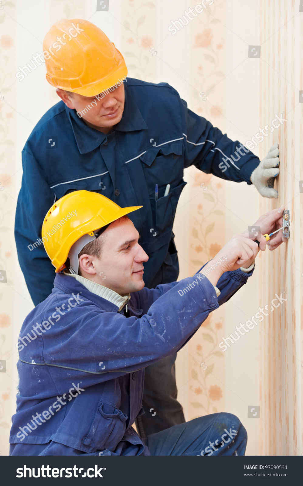 Two Electrician Workers At Wiring Cable And Light Switch Or Power Wall Outlets Id 97090544