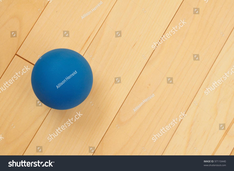 Blue rubber racquetball on hardwood court stock photo for Hardwood floors hurt feet