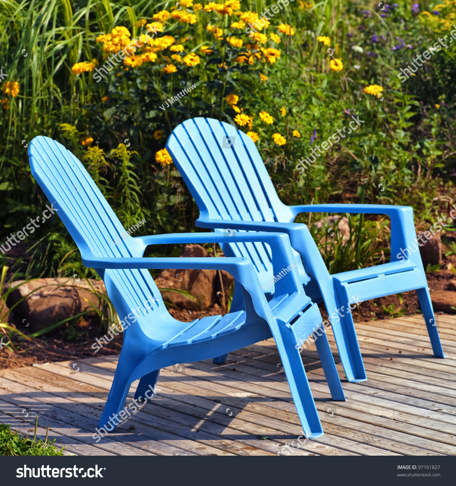 Exceptionnel Brilliant Blue Plastic Outdoor Adirondack Chairs On The Deck In A Summer  Garden.