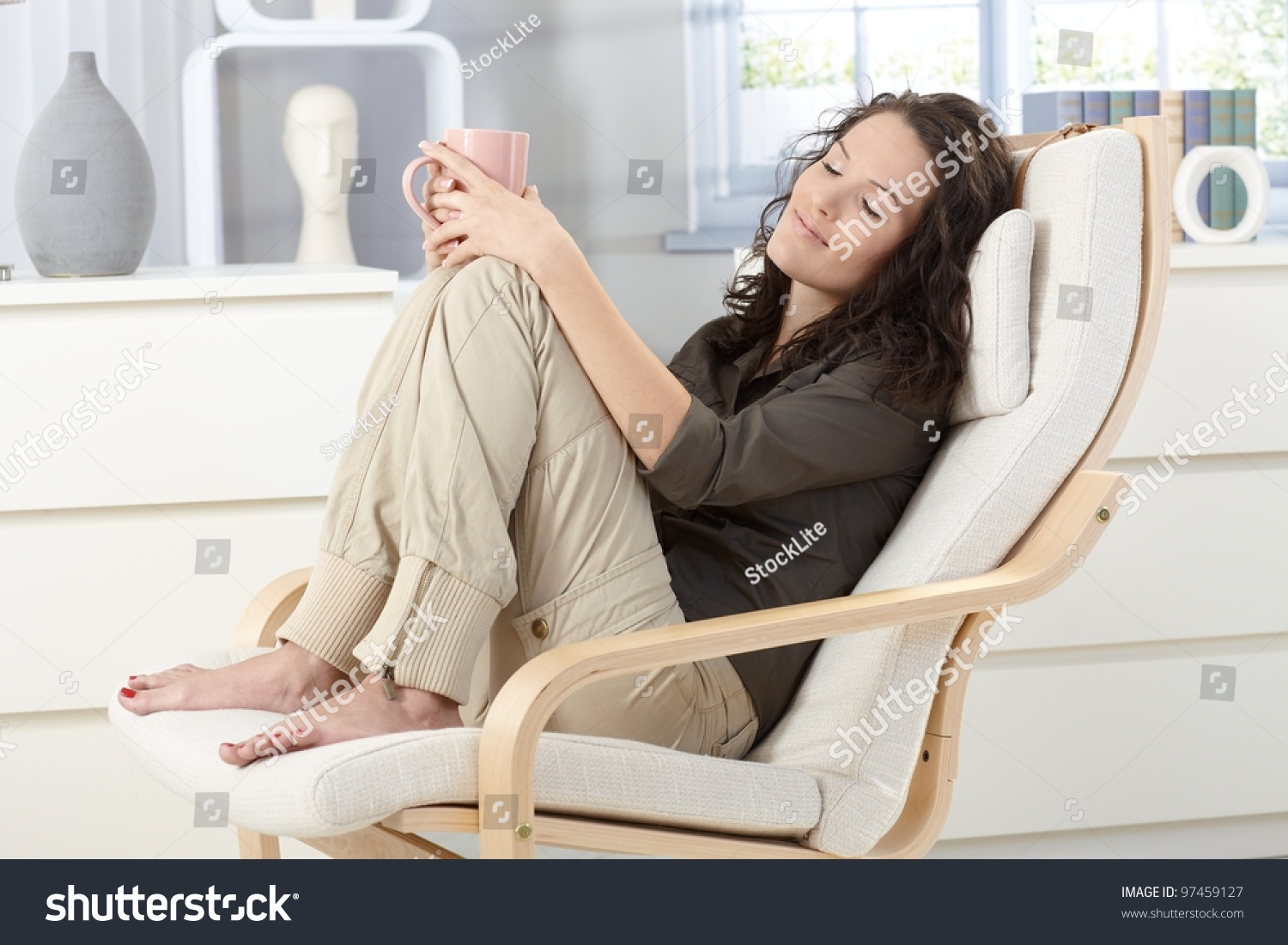 woman relaxing with closed eyes and cup of tea in armchair. Black Bedroom Furniture Sets. Home Design Ideas