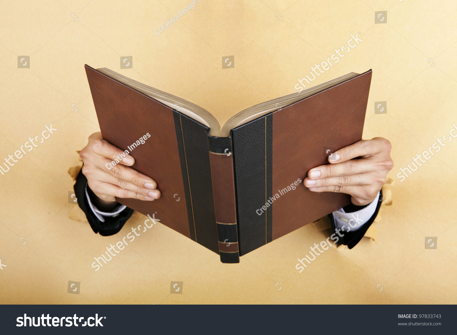 Technology Management Image: Businessman Hand Holding A Book Breaking Through A Paper