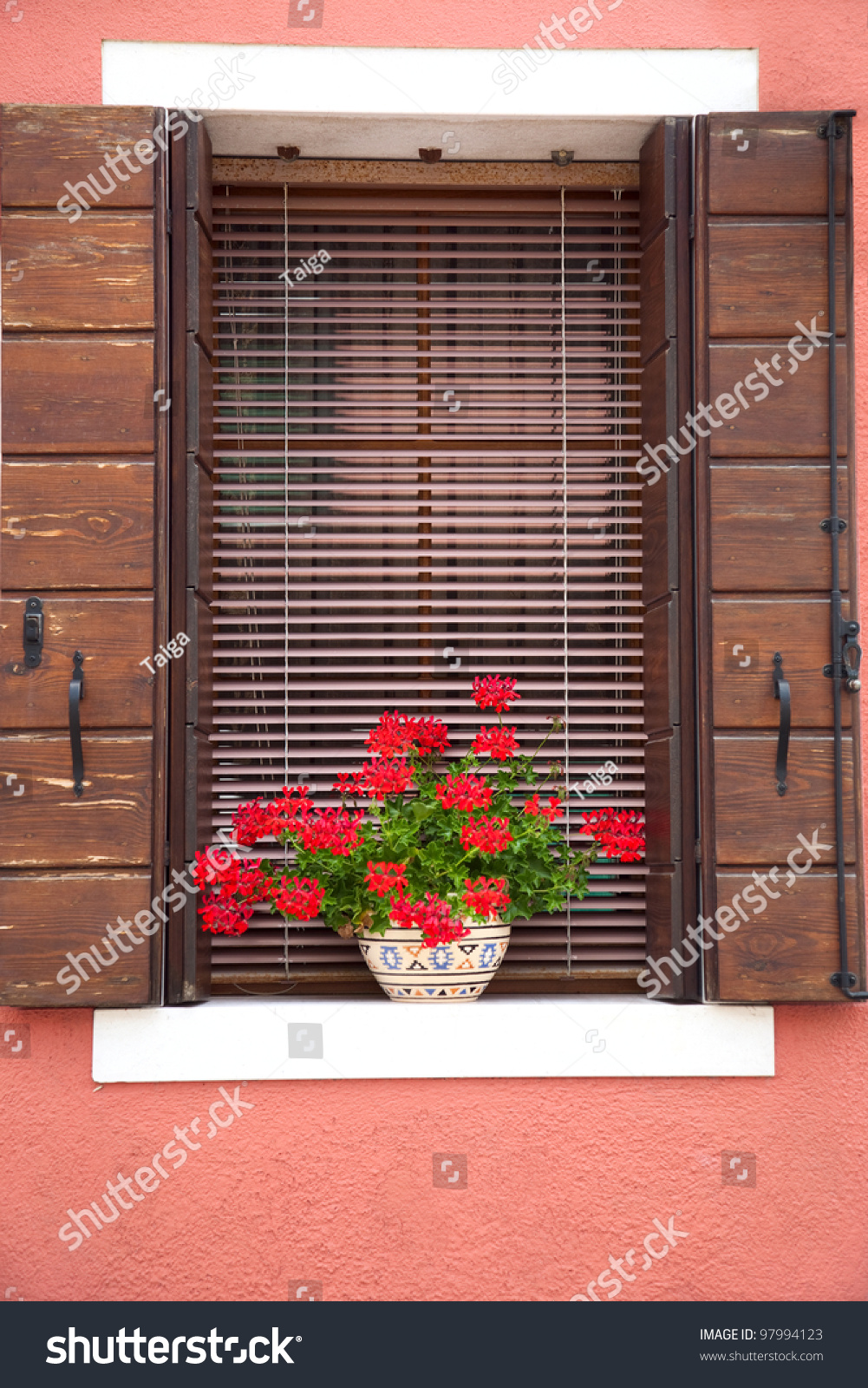 Old european window with flowers and wooden shutters for European shutters