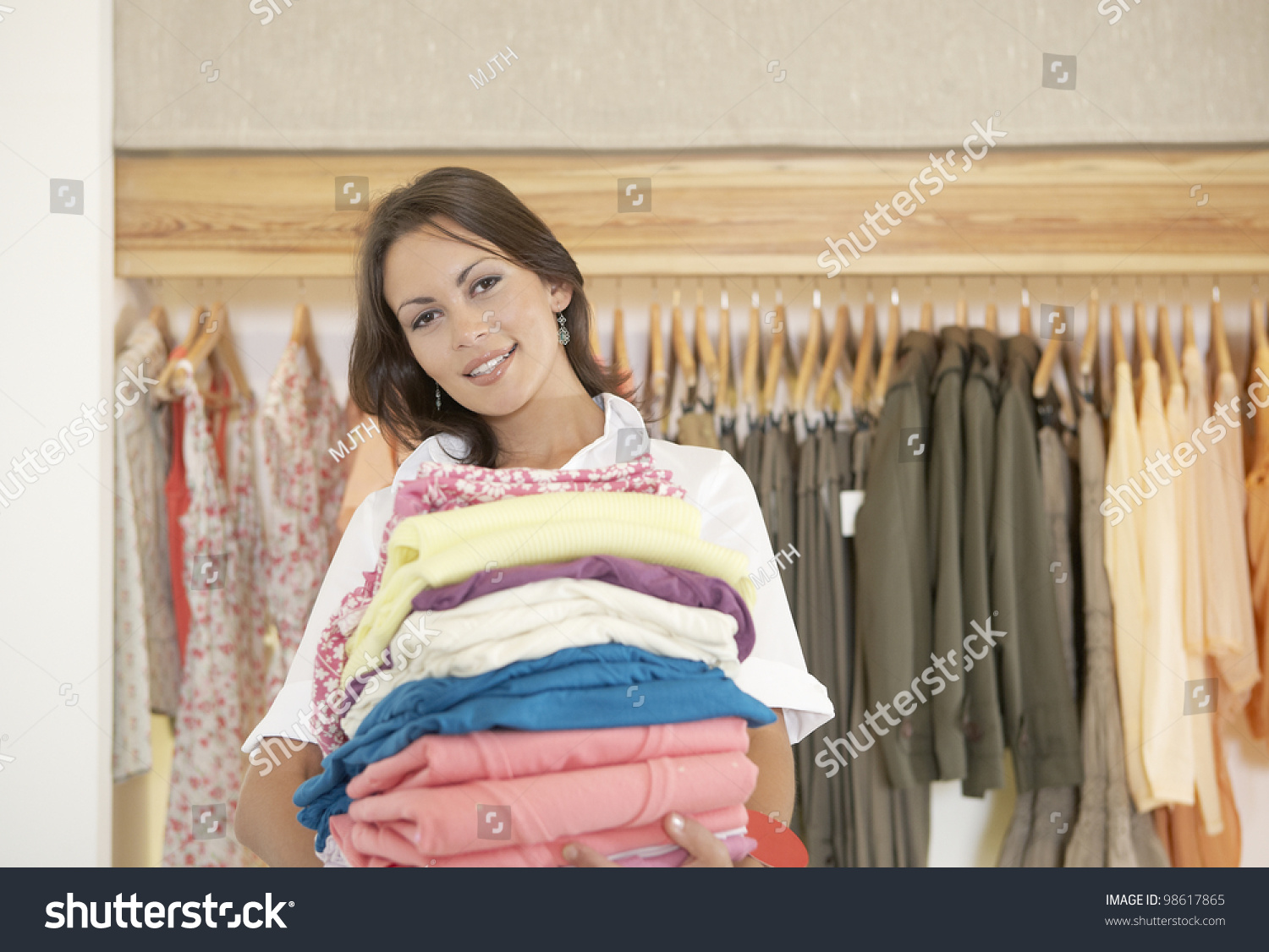 shop assistant holding pile clothes fashion stock photo  shop assistant holding a pile of clothes in a fashion store