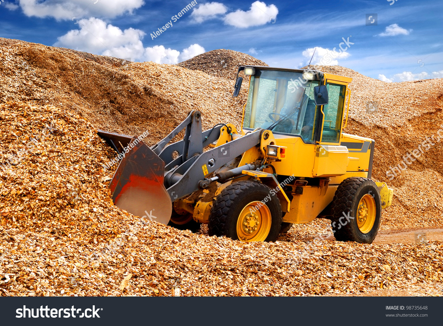 Bulldozer working in sawdust stock photo