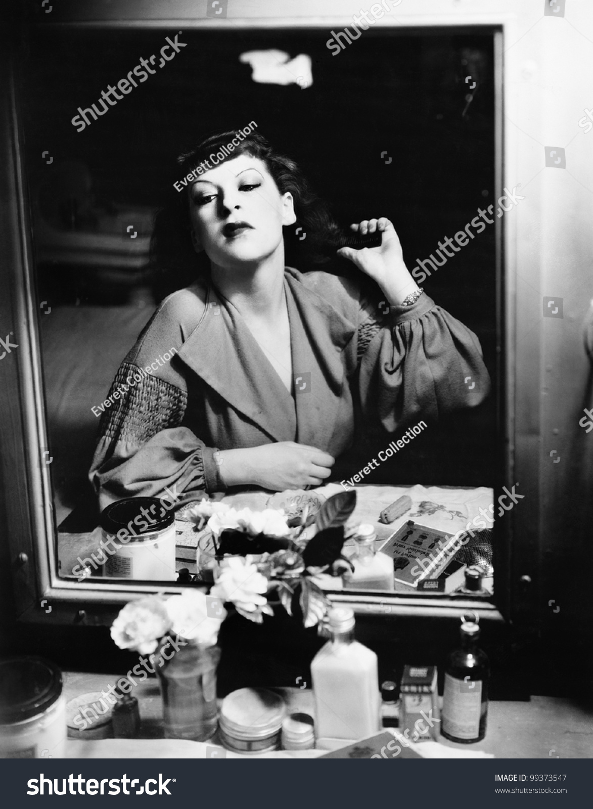 Woman Sitting In Front Of Her Vanity Looking Into The