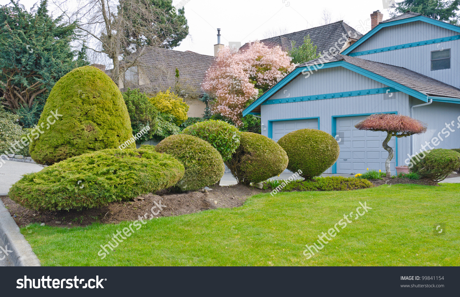 Landscape design nicely trimmed bushes at the front yard for Landscape design canada