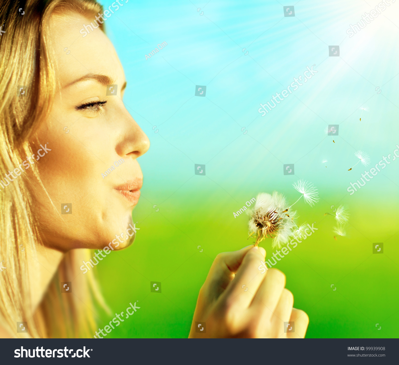 Happy Beautiful Woman Enjoying At Beach Stock Photo: Happy Beautiful Woman Blowing Dandelion Over Blur